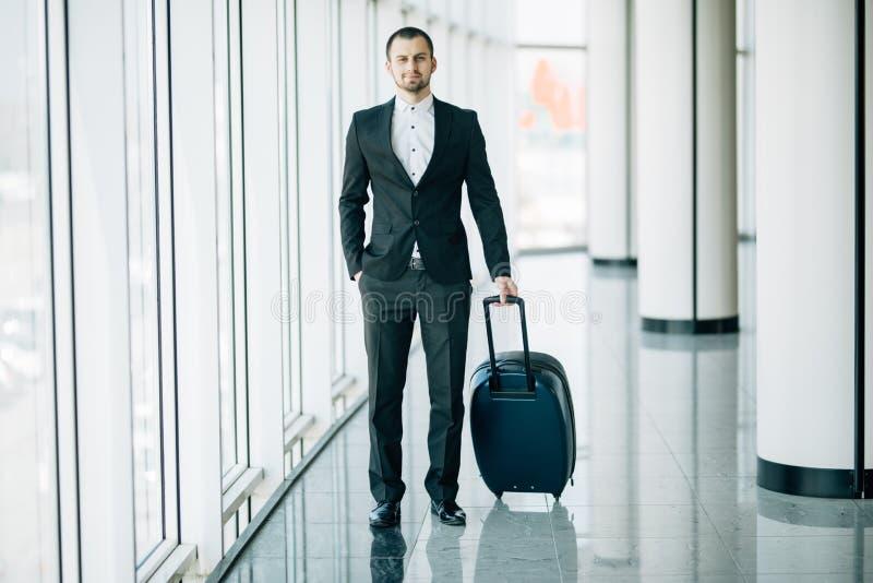 Ο επιχειρηματίας που σέρνει έναν μικρό συνεχίζει τη βαλίτσα αποσκευών στο διάδρομο αερολιμένων περπατώντας στις πύλες αναχώρησης  στοκ φωτογραφία