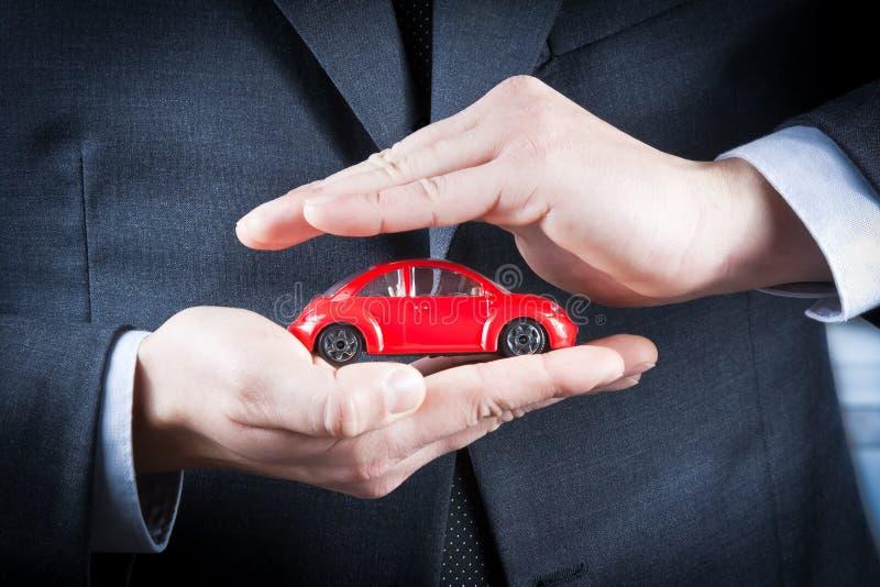 Ο επιχειρηματίας προστατεύει με τα χέρια του ένα κόκκινο αυτοκίνητο, την έννοια για την ασφάλεια, την αγορά, την ενοικίαση, τα καύ στοκ φωτογραφίες
