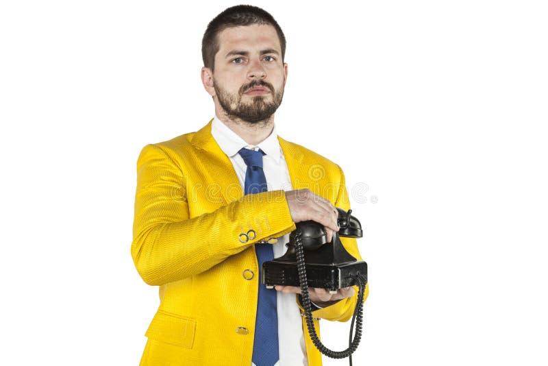 Ο επιχειρηματίας σε ένα χρυσό κοστούμι κλείνει το τηλέφωνο το τηλέφωνο στοκ φωτογραφία
