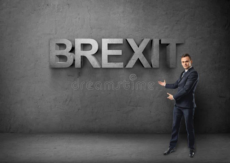 Ο επιχειρηματίας στέκεται μεγάλοι τρισδιάστατο & x27 brexit& x27  λέξη και από τα δύο χέρια στο συγκεκριμένο υπόβαθρο στοκ φωτογραφίες
