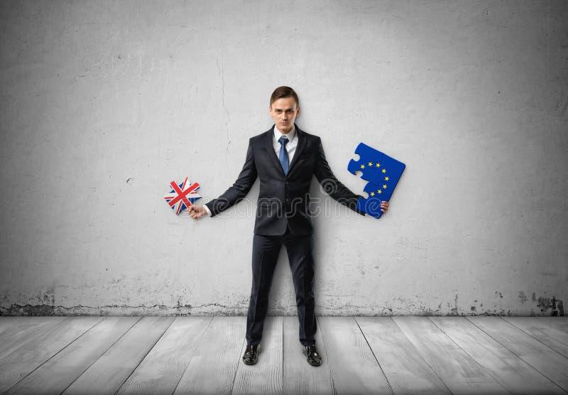 Ο επιχειρηματίας στέκεται τα κομμάτια του γρίφου με τις σημαίες της ΕΕ και του UK σε τους στοκ εικόνες