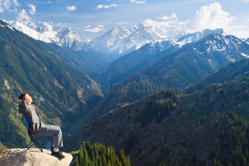 Ο επιχειρηματίας στην κορυφή του βουνού είναι ευτυχής με το α στοκ εικόνες με δικαίωμα ελεύθερης χρήσης