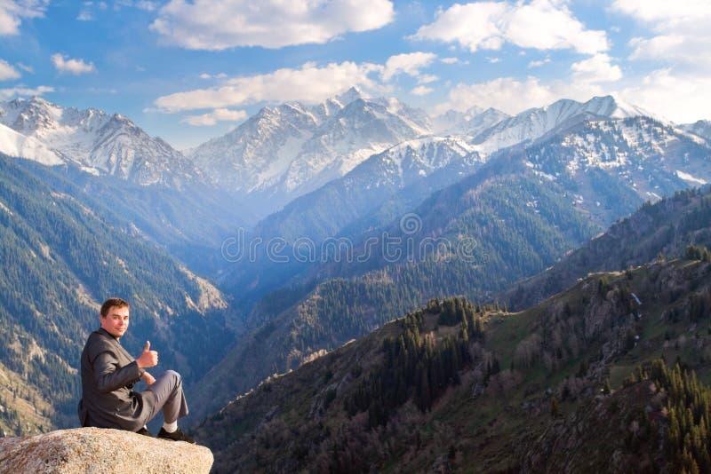 Ο επιχειρηματίας στην κορυφή του βουνού είναι ευτυχής με το α στοκ φωτογραφία με δικαίωμα ελεύθερης χρήσης