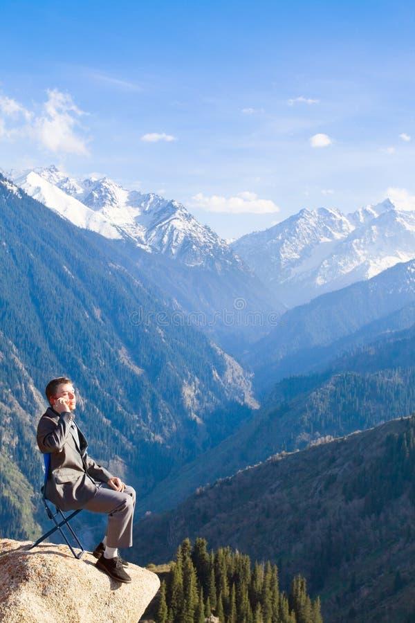 Ο επιχειρηματίας στην κορυφή του βουνού μιλά για νέο στοκ εικόνες