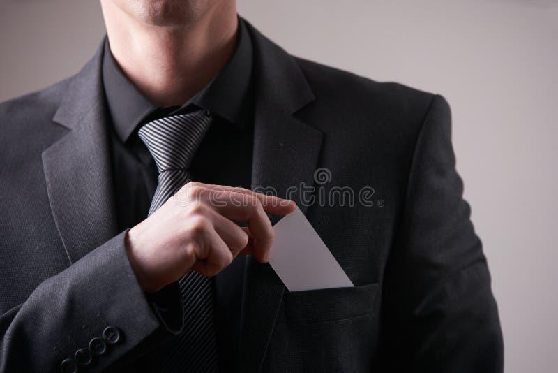 Ο επιχειρηματίας στο μαύρο κοστούμι και η γκρίζα γραβάτα βάζουν ή παίρνουν έξω την κάρτα επίσκεψης στην τσέπη στοκ φωτογραφίες με δικαίωμα ελεύθερης χρήσης