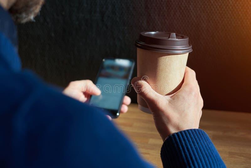 Ο επιχειρηματίας στο μπλε πουλόβερ πίνει τον καφέ σε έναν ηλιόλουστο καφέ, η κινηματογράφηση σε πρώτο πλάνο κρατά ένα μίας χρήσης στοκ εικόνα