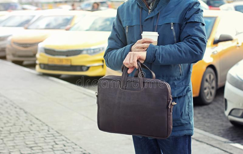 Ο επιχειρηματίας στο περιστασιακό σακάκι με την τσάντα και το φλιτζάνι του καφέ δέρματος στέκεται στο δρόμο πόλεων με το ταξί στο στοκ εικόνα