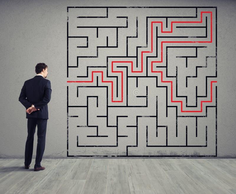 Ο επιχειρηματίας σύρει τη λύση ενός λαβύρινθου Έννοια της επίλυσης προβλήματος στοκ εικόνα