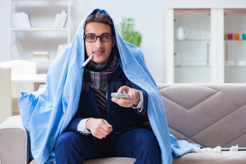 Ο επιχειρηματίας υπαλλήλων που προσέχει τη TV ενώ όντας άρρωστος με τη γρίπη στοκ φωτογραφία με δικαίωμα ελεύθερης χρήσης
