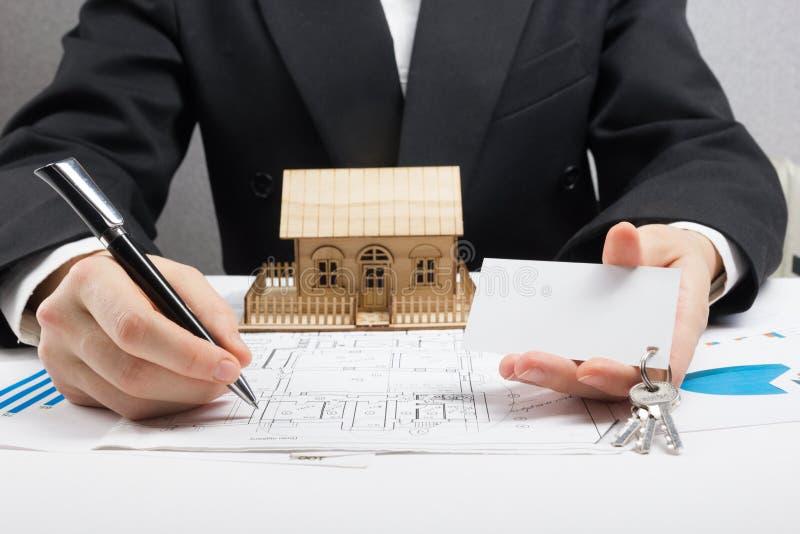 Ο επιχειρηματίας υπογράφει τη σύμβαση πίσω από το εγχώριο αρχιτεκτονικό πρότυπο στοκ φωτογραφία