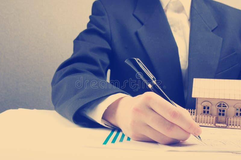 Ο επιχειρηματίας υπογράφει τη σύμβαση πίσω από το εγχώριο αρχιτεκτονικό πρότυπο στοκ εικόνα