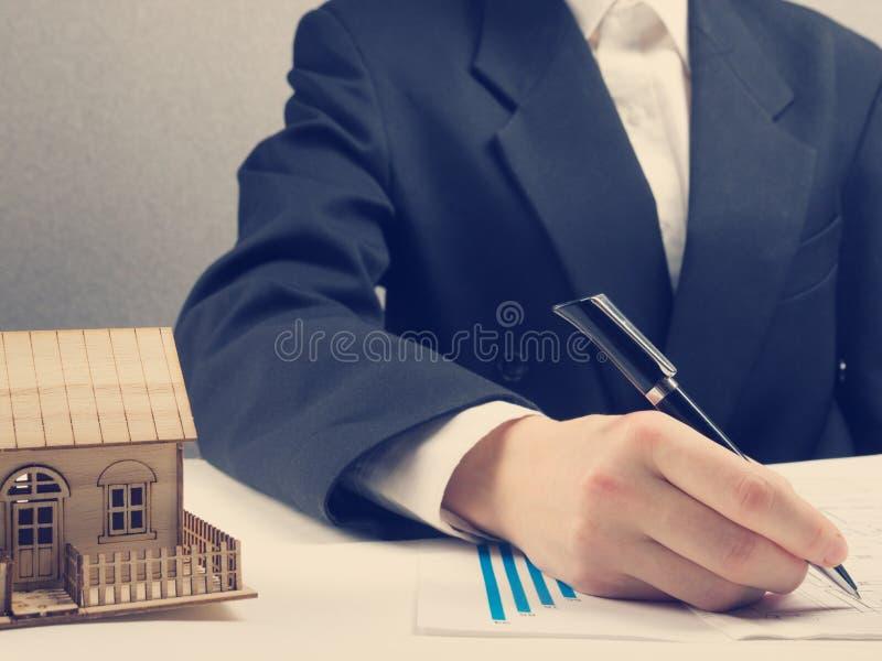 Ο επιχειρηματίας υπογράφει τη σύμβαση πίσω από το εγχώριο αρχιτεκτονικό πρότυπο στοκ φωτογραφία με δικαίωμα ελεύθερης χρήσης