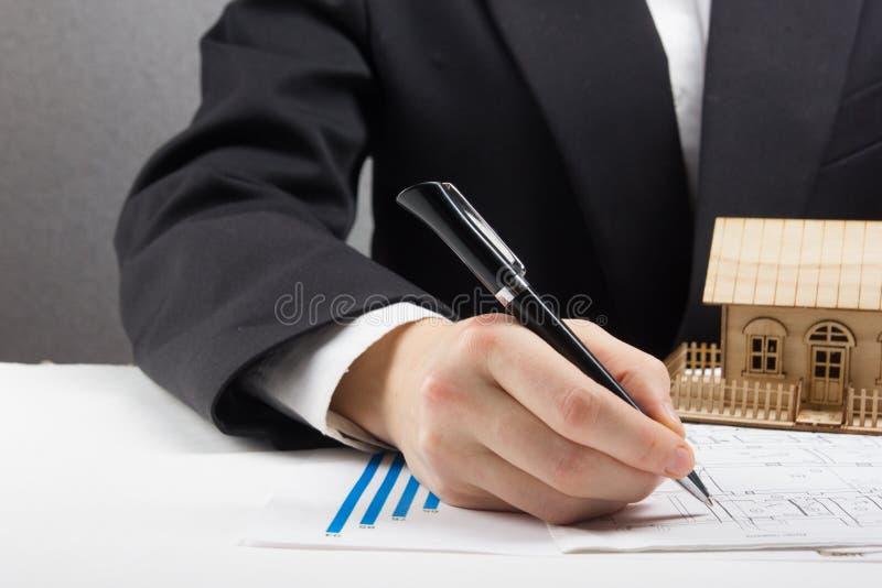 Ο επιχειρηματίας υπογράφει τη σύμβαση πίσω από το εγχώριο αρχιτεκτονικό πρότυπο στοκ φωτογραφίες
