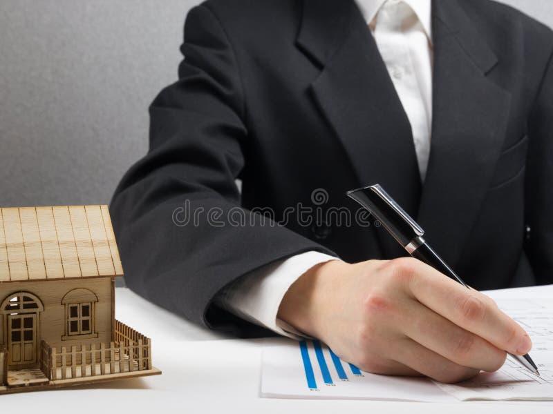 Ο επιχειρηματίας υπογράφει τη σύμβαση πίσω από το εγχώριο αρχιτεκτονικό πρότυπο στοκ εικόνες