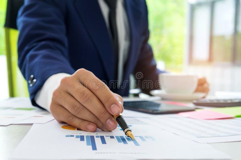 Ο επιχειρηματίας χρησιμοποιεί μια μάνδρα δείχνοντας στο διάγραμμα για να αναλύσει τα στοιχεία στοκ φωτογραφία