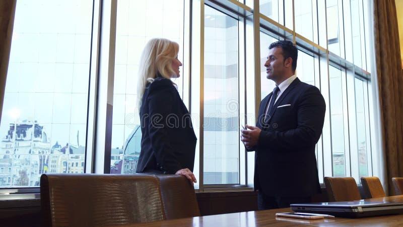 Ο επιχειρησιακοί άνδρας και η γυναίκα υπερασπίζονται το πανοραμικό παράθυρο στο γραφείο τους στοκ φωτογραφία με δικαίωμα ελεύθερης χρήσης