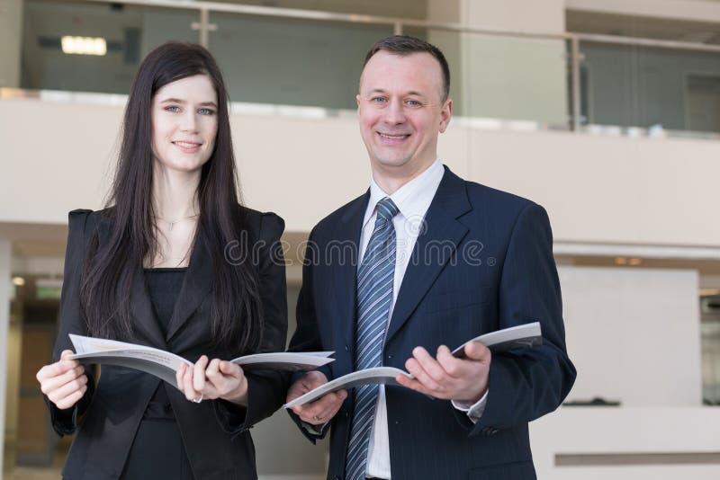 Ο επιχειρησιακοί άνδρας και η γυναίκα κρατούν τα περιοδικά στοκ εικόνες με δικαίωμα ελεύθερης χρήσης
