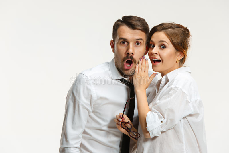 Ο επιχειρησιακοί άνδρας και η γυναίκα που επικοινωνούν σε ένα γκρίζο υπόβαθρο στοκ φωτογραφία