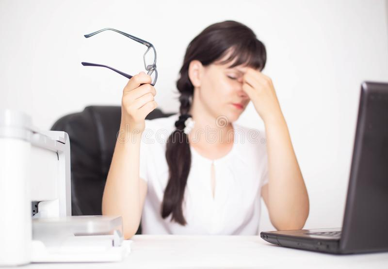 Ο επιχειρησιακός εργαζόμενος κοριτσιών στο γραφείο κρατά τα γυαλιά διαθέσιμα Έννοια του πόνου στα μάτια από τον υπολογιστή, σύνδρ στοκ εικόνα