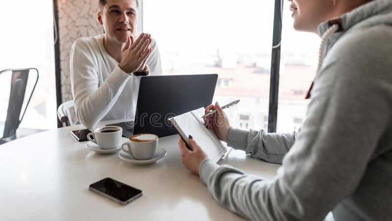 Ο επιχειρησιακός σύμβουλος ατόμων λέει σε έναν θηλυκό διευθυντή για τη χρηματοοικονομική απόδοση Μια γυναίκα κάνει τις σημειώσεις στοκ εικόνες