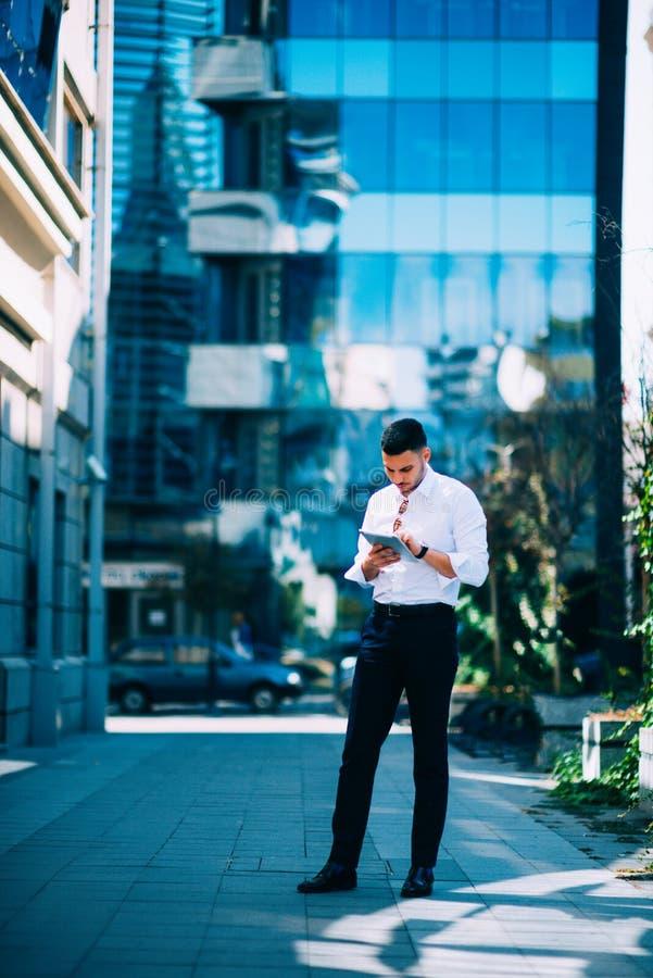 Ο επιχειρησιακός τύπος που φορά το άσπρο πουκάμισο χαμογελά και κρατά την ταμπλέτα επιχειρηματίας αστικός στοκ φωτογραφίες με δικαίωμα ελεύθερης χρήσης