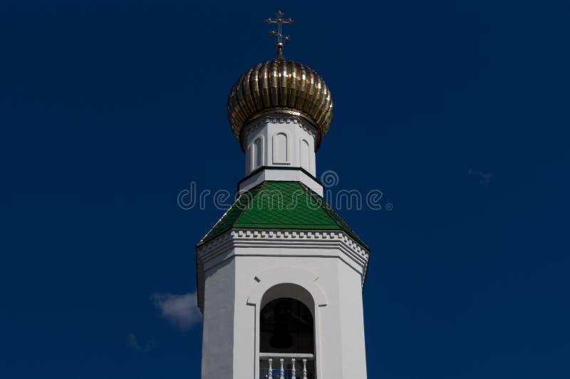 Ο επιχρυσωμένος θόλος του πύργου κουδουνιών, η εκκλησία στα πλαίσια του νεφελώδους ουρανού στοκ εικόνες