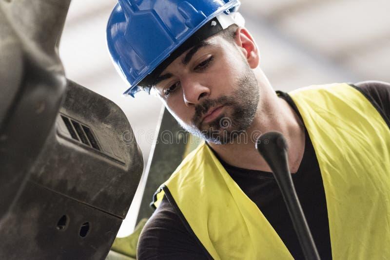 Ο εργάτης οικοδομών αναθεωρεί τη λειτουργώντας μηχανή στοκ εικόνες με δικαίωμα ελεύθερης χρήσης