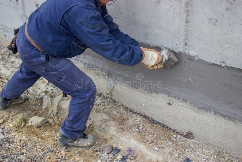 Ο εργάτης οικοδομών με τη βούρτσα εφάρμοσε την υδρο μόνωση 2 στοκ εικόνα