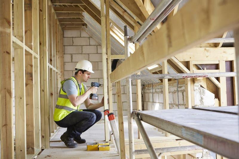 Ο εργάτης οικοδομών που χρησιμοποιεί το τρυπάνι στο σπίτι χτίζει στοκ εικόνες