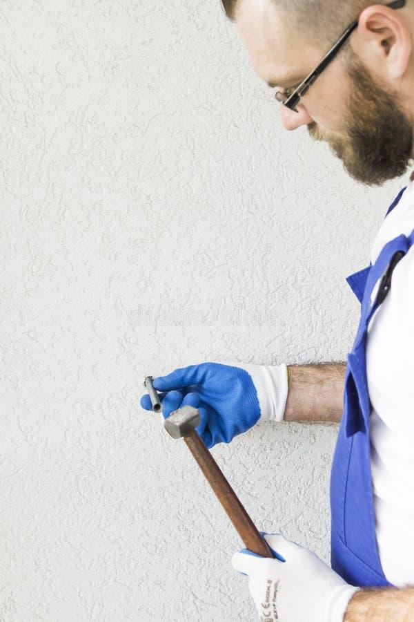 Ο εργάτης οικοδομών ` s παραδίδει τα προστατευτικά γάντια συνδέει το μπουλόνι αγκύρων με τον τοίχο του κτηρίου στοκ φωτογραφία με δικαίωμα ελεύθερης χρήσης