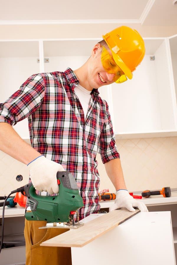 Ο εργαζόμενος απασχολείται στο τορνευτικό πριόνι στοκ φωτογραφία