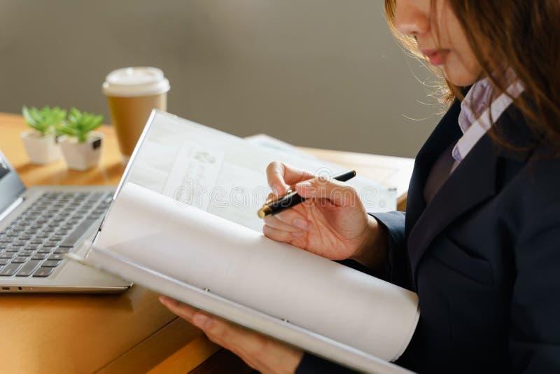 Ο εργαζόμενος γραφείων θηλυκών φορά το σκούρο μπλε επιχειρησιακό κοστούμι που λειτουργεί με το αρχείο εγγράφων και το σωρό του εγ στοκ εικόνες