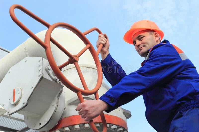 Ο εργαζόμενος γυρίζει τη βαλβίδα στοκ φωτογραφία με δικαίωμα ελεύθερης χρήσης