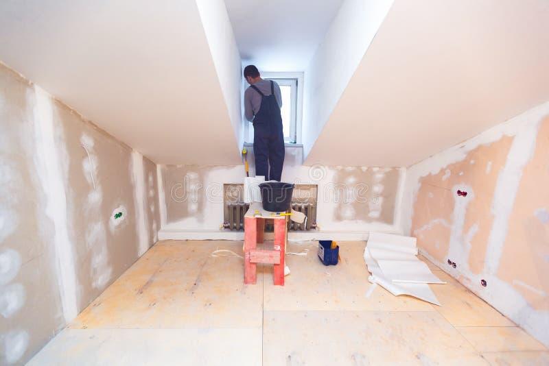 Ο εργαζόμενος εγκαθιστά το παράθυρο PVC από την ξύλινη πλατφόρμα στο μικρό δωμάτιο του διαμερίσματος που είναι κάτω από την κατασ στοκ φωτογραφία με δικαίωμα ελεύθερης χρήσης