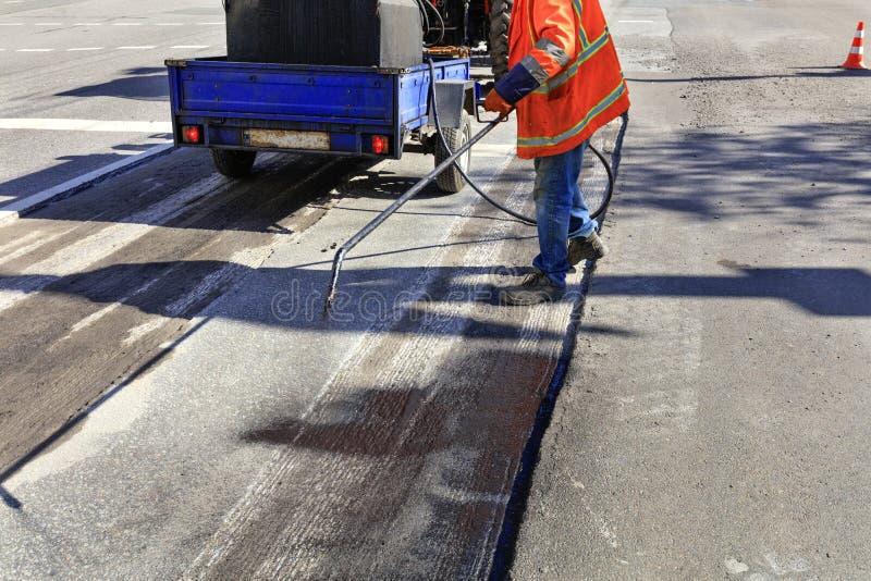 Ο εργαζόμενος επισκευάζει μέρος του δρόμου ασφάλτου, που ψεκάζει την πίσσα στην επιφάνεια ασφάλτου στοκ εικόνα