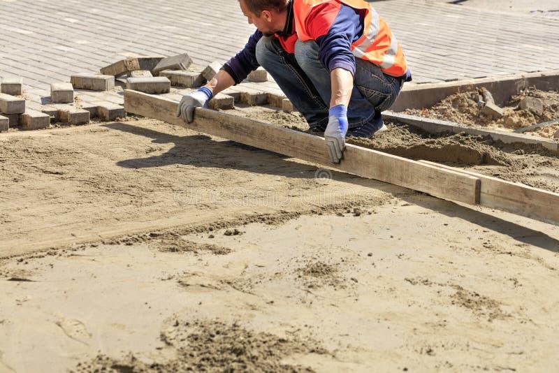 Ο εργαζόμενος ευθυγραμμίζει τη βάση άμμου με έναν ξύλινο πίνακα για την τοποθέτηση των πλακών επίστρωσης στο πεζοδρόμιο στοκ φωτογραφίες