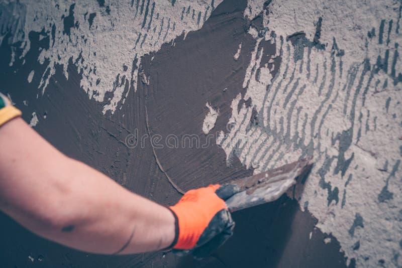 Ο εργαζόμενος ευθυγραμμίζει τον τοίχο με μια κόλλα κεραμιδιών εφαρμόζοντας τον με spatula στοκ εικόνα με δικαίωμα ελεύθερης χρήσης
