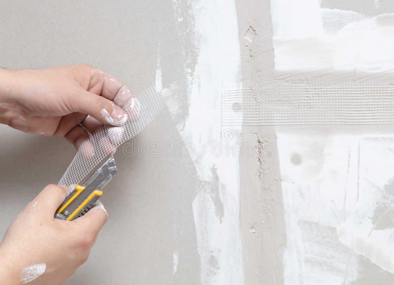 Ο εργαζόμενος ευθυγραμμίζει τους τοίχους με το ασβεστοκονίαμα Επισκευή στο σπίτι στοκ εικόνες με δικαίωμα ελεύθερης χρήσης