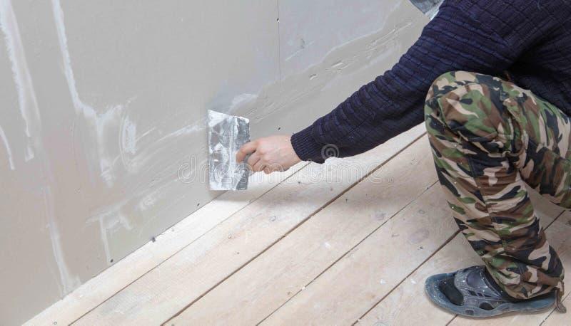 Ο εργαζόμενος ευθυγραμμίζει τους τοίχους με το ασβεστοκονίαμα Επισκευή στο σπίτι στοκ φωτογραφία με δικαίωμα ελεύθερης χρήσης