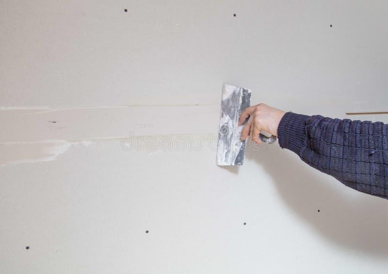Ο εργαζόμενος ευθυγραμμίζει τους τοίχους με το ασβεστοκονίαμα Επισκευή στο σπίτι στοκ εικόνα με δικαίωμα ελεύθερης χρήσης