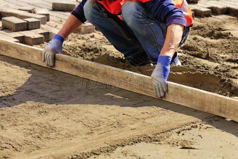 Ο εργαζόμενος ευθυγραμμίζει το ίδρυμα με μια ξύλινη σανίδα για τα ομαλά κεραμίδια τοποθέτησης στο πεζοδρόμιο στοκ εικόνες