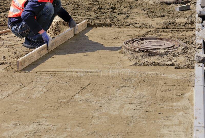 Ο εργαζόμενος ευθυγραμμίζει το αμμώδες ίδρυμα με έναν ξύλινο πίνακα για την τοποθέτηση των κεραμιδιών γύρω από την καταπακτή υπον στοκ φωτογραφία με δικαίωμα ελεύθερης χρήσης