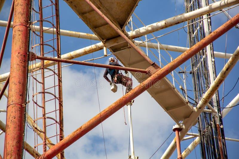 Ο εργαζόμενος ζωγραφίζει σωλήνες σε ύψος, βιομηχανική ορειβασία, ζωγραφίζοντας ψηλά κτίρια και αντικείμενα στοκ φωτογραφία