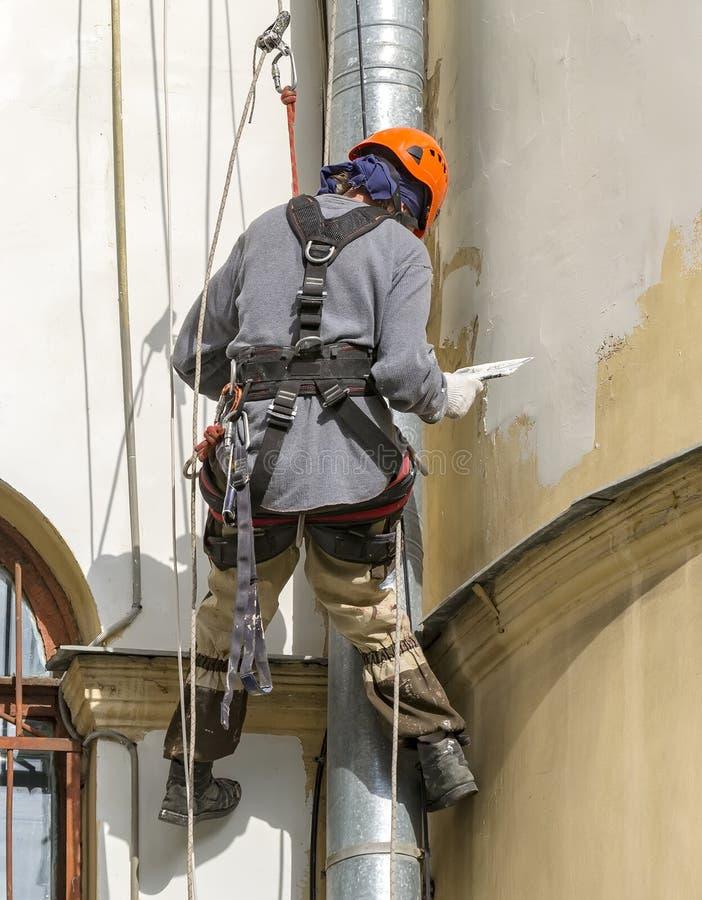Ο εργαζόμενος κάνει τις καλλυντικές επισκευές της πρόσοψης του σπιτιού r r Σπίτι 55 λεωφόρων χυτηρίων στοκ εικόνες