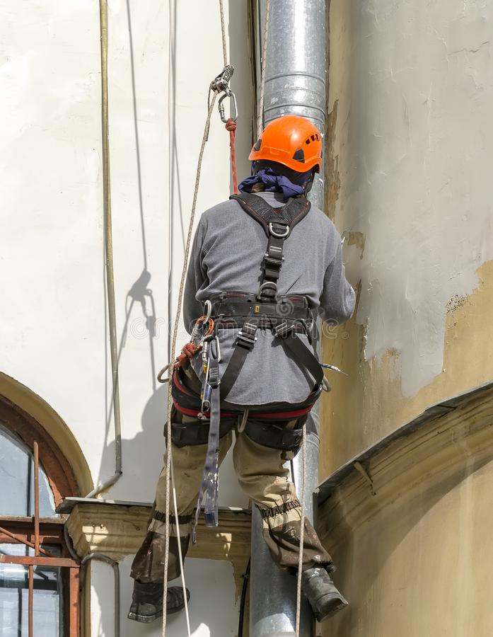 Ο εργαζόμενος κάνει τις καλλυντικές επισκευές της πρόσοψης του σπιτιού r r Σπίτι 55 λεωφόρων χυτηρίων στοκ φωτογραφίες με δικαίωμα ελεύθερης χρήσης