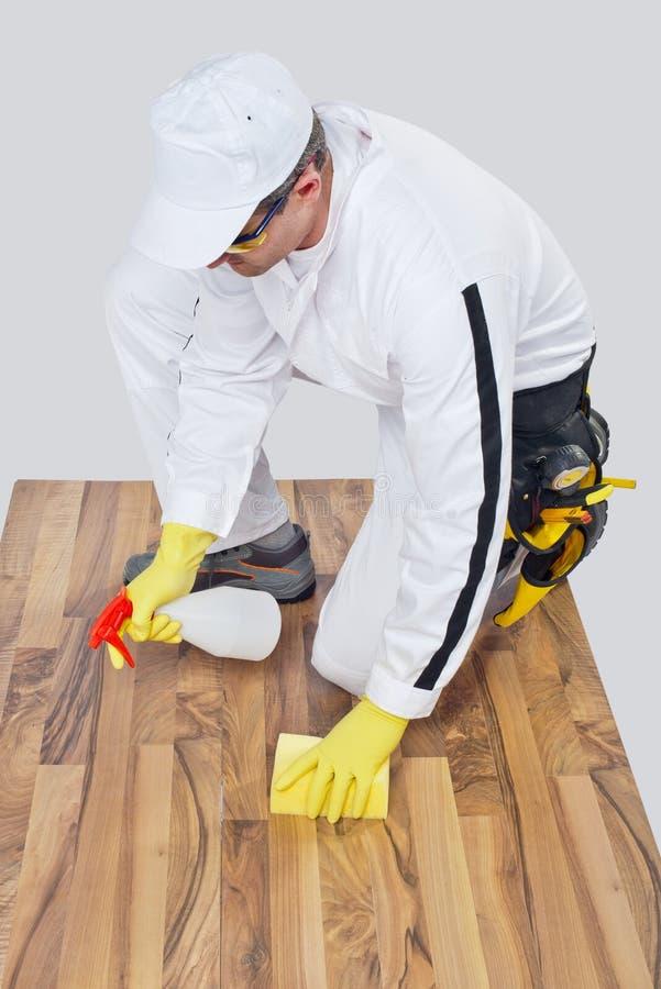 Ο εργαζόμενος καθαρίζει με το ξύλινο πάτωμα σφουγγαριών και ψεκασμού πρίν οργώνει στοκ εικόνες με δικαίωμα ελεύθερης χρήσης