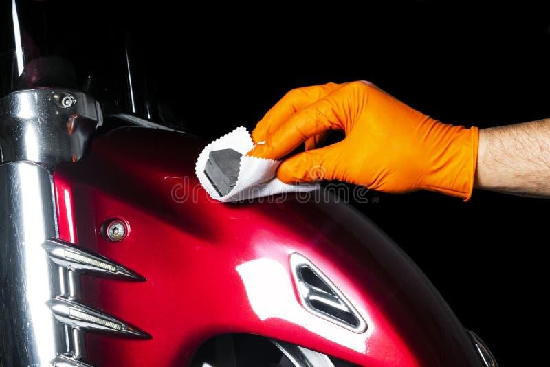 Ο εργαζόμενος κεριών στιλβωτικής ουσίας αυτοκινήτων δίνει τη γυαλίζοντας μοτοσικλέτα Buffing και στίλβωσης όχημα με κεραμικό Απαρ στοκ φωτογραφία