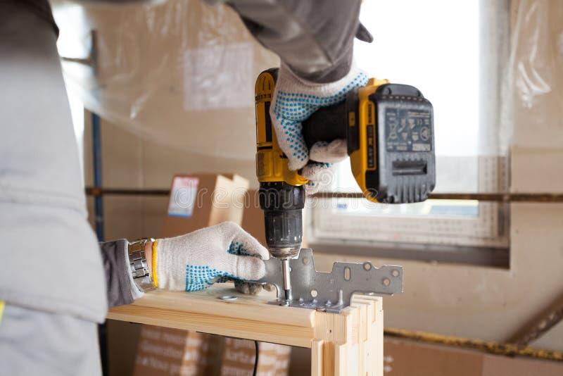 Ο εργαζόμενος κτιστών κατασκευής συνδέει το μέταλλο παραθύρων που εγκαθιστά με το φεγγίτη στοκ φωτογραφία