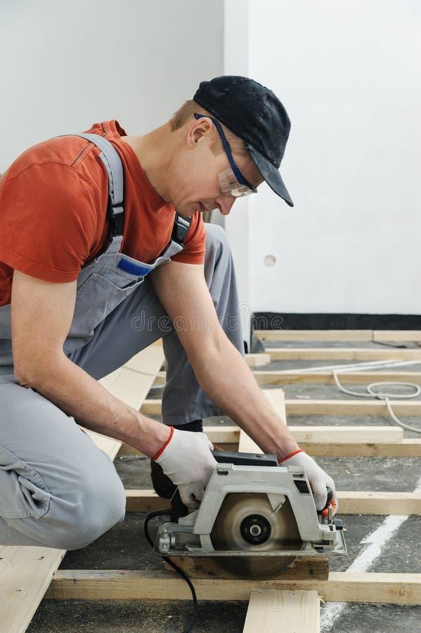 Ο εργαζόμενος κόβει ξύλινα floorboards στοκ εικόνες