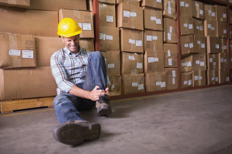 Ο εργαζόμενος με ο αστράγαλος στο πάτωμα στην αποθήκη εμπορευμάτων στοκ φωτογραφίες